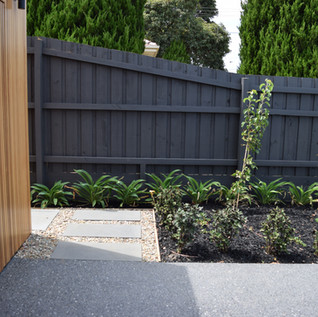 Exposed aggregate concrete driveway leading into Bluestone steppers pathway surrounded with river pebbles