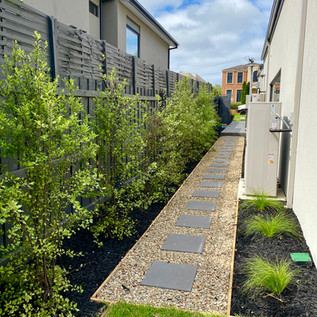 Side pathway of Bluestone steppers with river pebbles and timber edged garden beds with black mulch