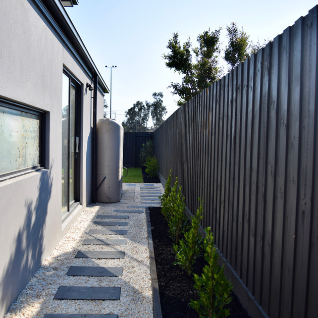 White pebbled Bluestone stepper pathway with timber edged garden beds and painted Monument timber paling fencing