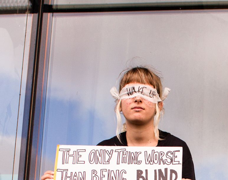 """A girl sits blindfolded with a sign that reads """"The only thing worse than being blind is having sight but no vision,"""" at the first general climate strike in Den Haag, The Netherlands, on September 27, 2019. Building on the youth climate strikes that began almost a year ago, an estimated 35,000 people of all ages gathered to demand change in Dutch and international climate policy. The strike was a part of the largest international climate mobilization in history."""