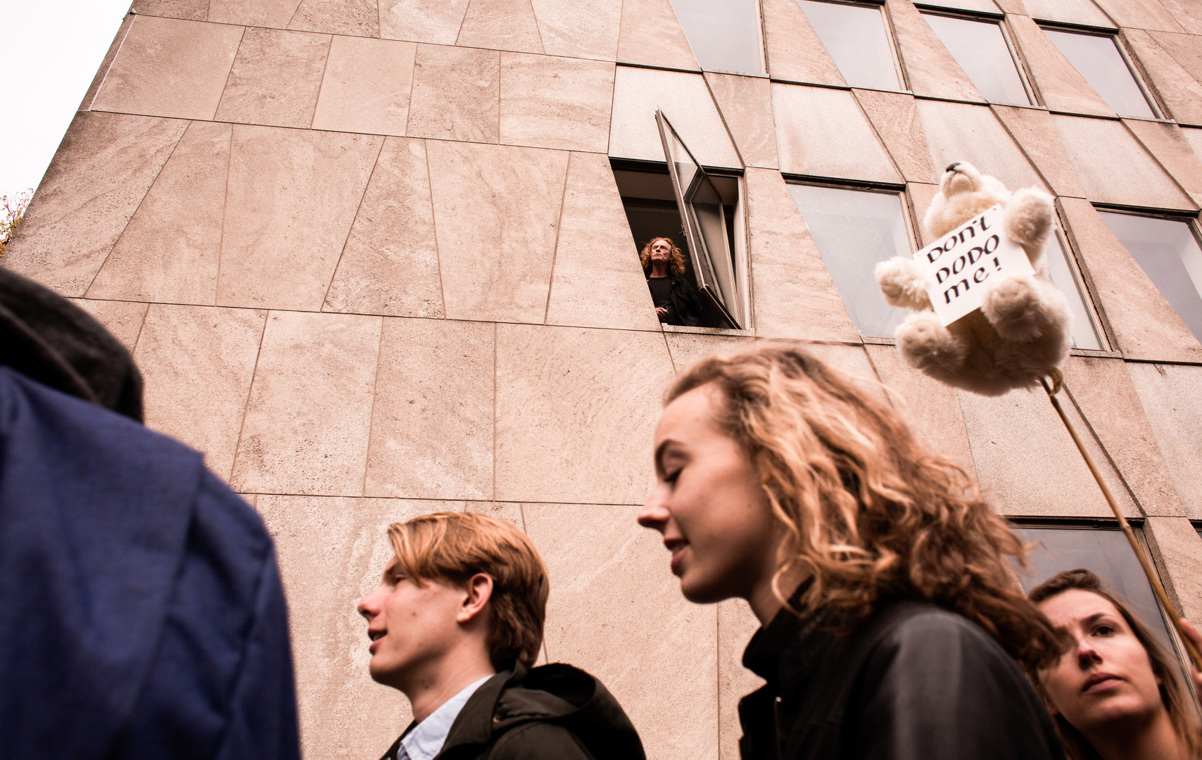 Someone watches out his window as the street is filled with protestors at the first general climate strike in Den Haag, The Netherlands, on September 27, 2019. Building on the youth climate strikes that began almost a year ago, an estimated 35,000 people of all ages gathered to demand change in Dutch and international climate policy. The strike was a part of the largest international climate mobilization in history.