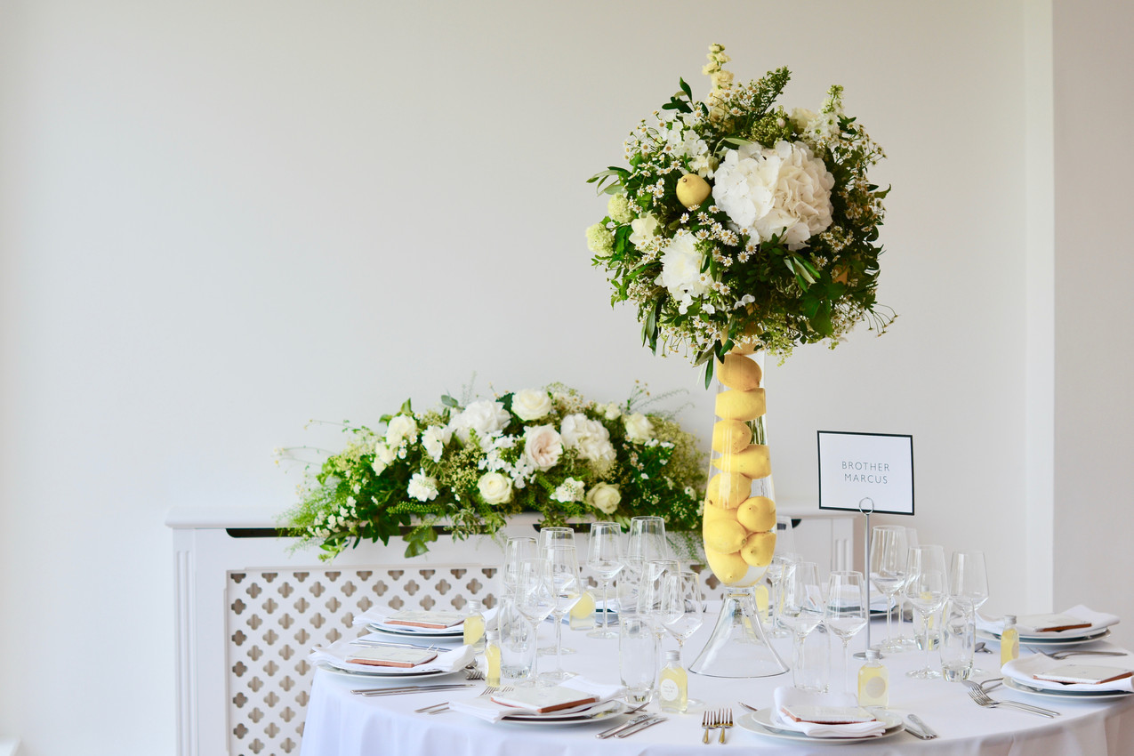 Nine tables contained tall hour glass vases (75 cm) that were filled with lemons and topped up with water, which magnified the bright yellow fruit. Each vase was complete with a sphere of lush greenery including variegated pittosporum, pistachio, vibernum snowball, lace-cap hydrangeas and complemented with ivory and white Snowball hydrangeas, stocks, matricaria feverfew, Avalanche roses and a lemon or two. Radiator dressed with a long and low arrangement of coordinating flowers and foliage.