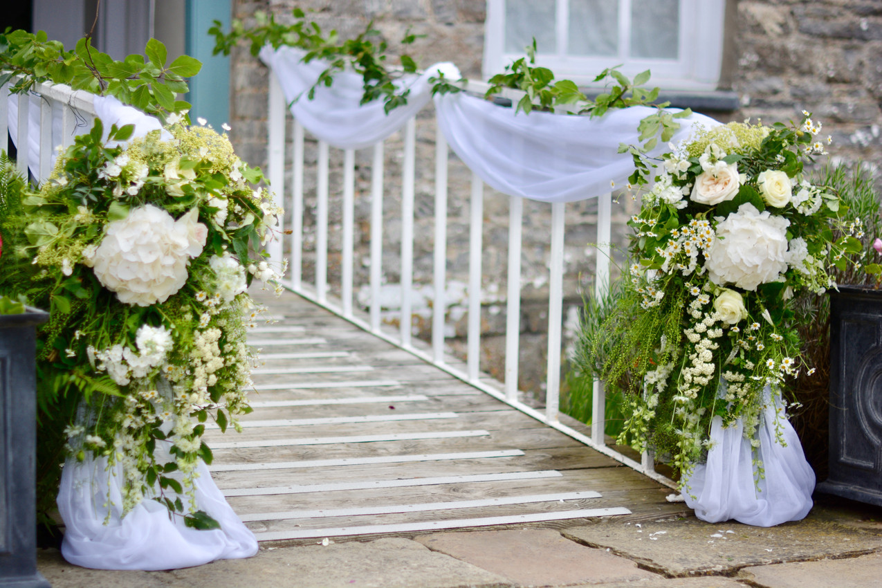 Image indicated the footbridge decorated with ivory muslin and coordinating floral arrangements of ivory, white seasonal flowers and greenery.