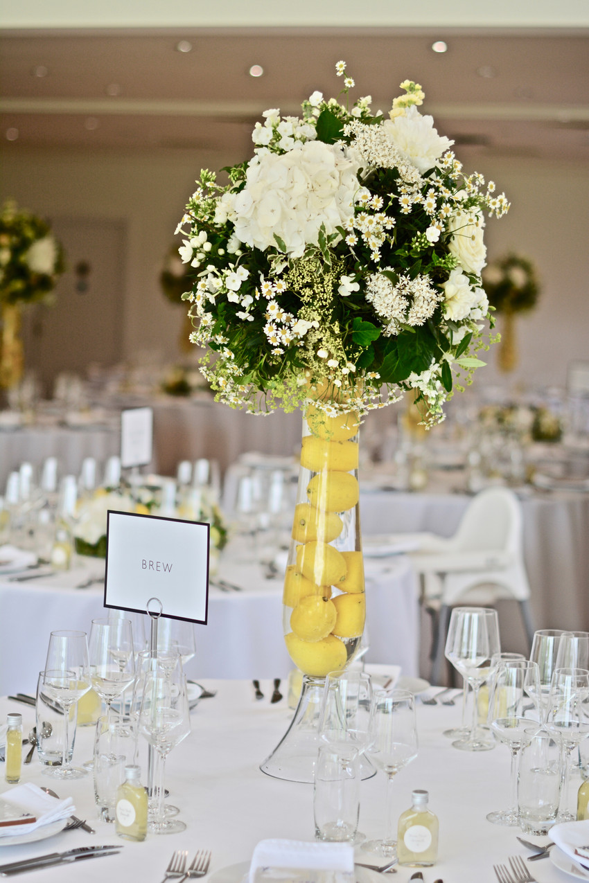 Nine tables contained tall hour glass vases (75 cm) that were filled with lemons and topped up with water, which magnified the bright yellow fruit. Each vase was complete with a sphere of lush greenery including variegated pittosporum, pistachio, vibernum snowball, lace-cap hydrangeas and complemented with ivory and white Snowball hydrangeas, stocks, matricaria feverfew, Avalanche roses and a lemon or two.