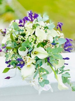 Shower bouquet of white phalanopsis orchids, lily of the valley, eucalyptus and clematis