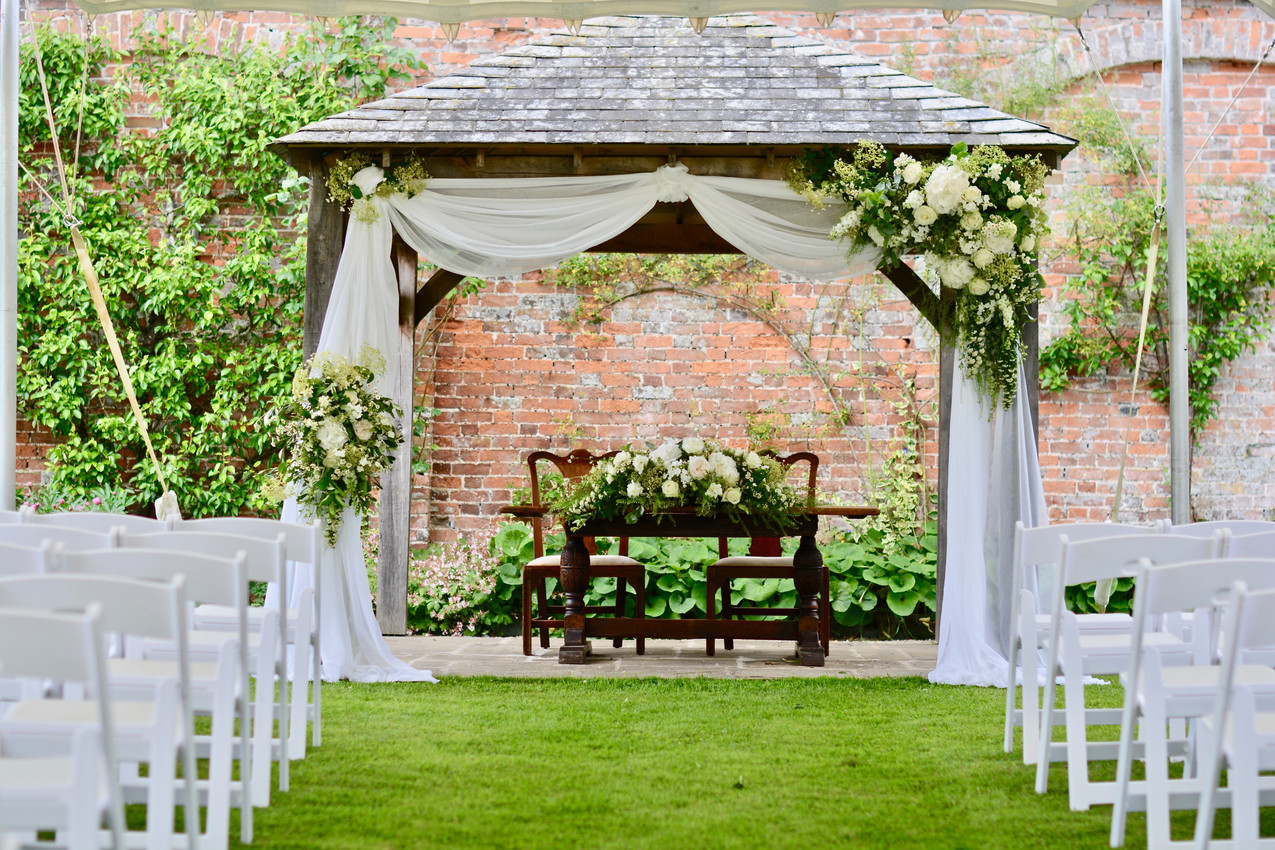 The ceremony gazebo is decorated with with swags of ivory muslin, complete with a large top right corner arrangement of coordinating flowers and greenery with a smaller opposite lower side arrangement. Register Table decorated with a complementary long and low arrangement.