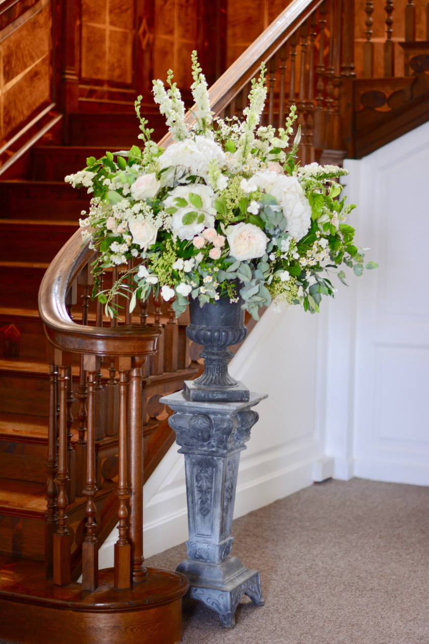 and a tall classical pedestal and urn at the foot of the staircase.