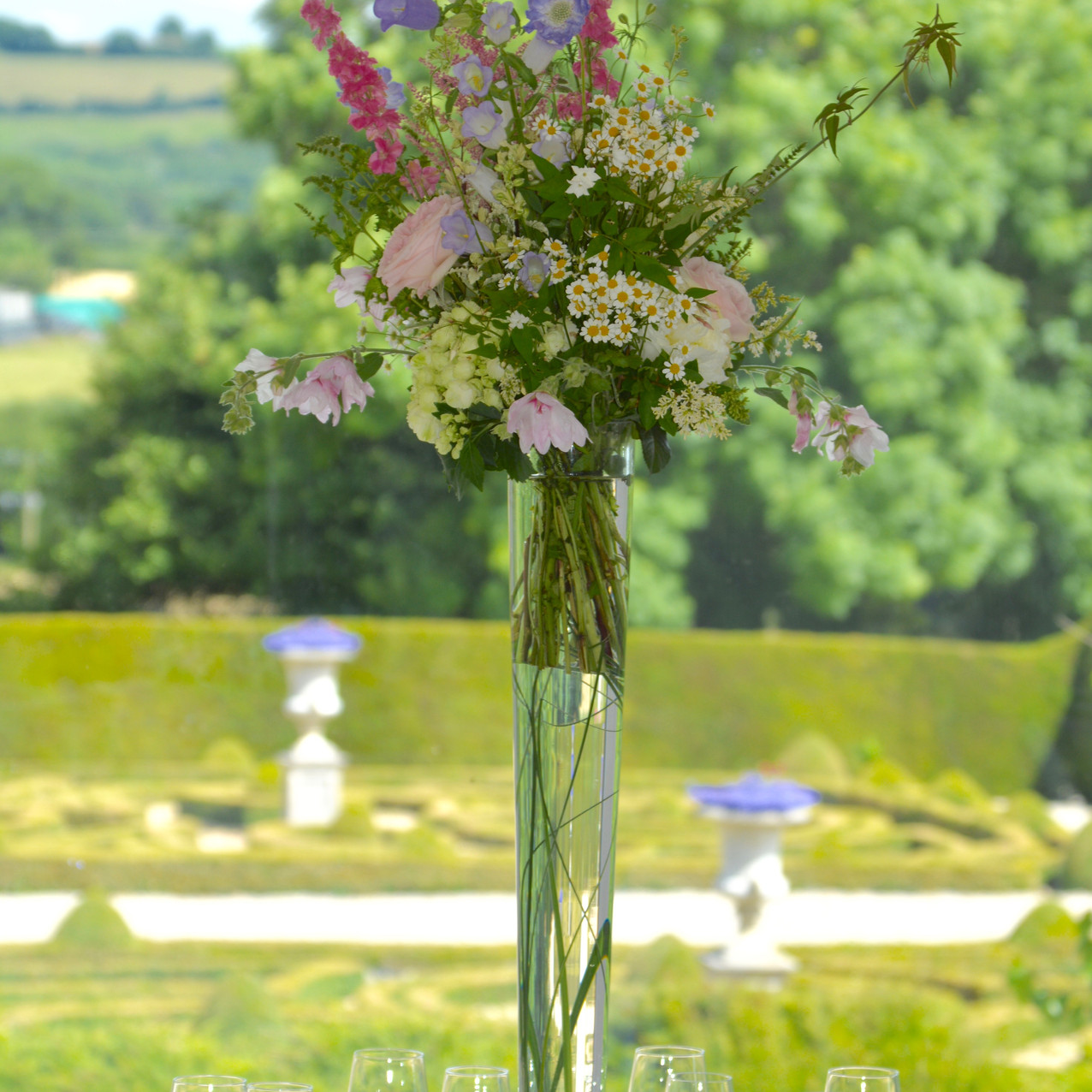 Tall conic vase with hand-tied arrangement of summer flowers