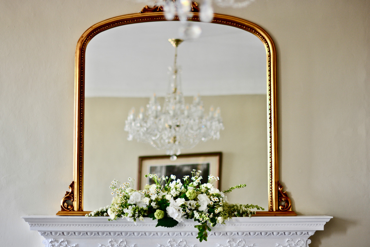 a lush green and white long and low on the mantle-piece in the Marble Hall