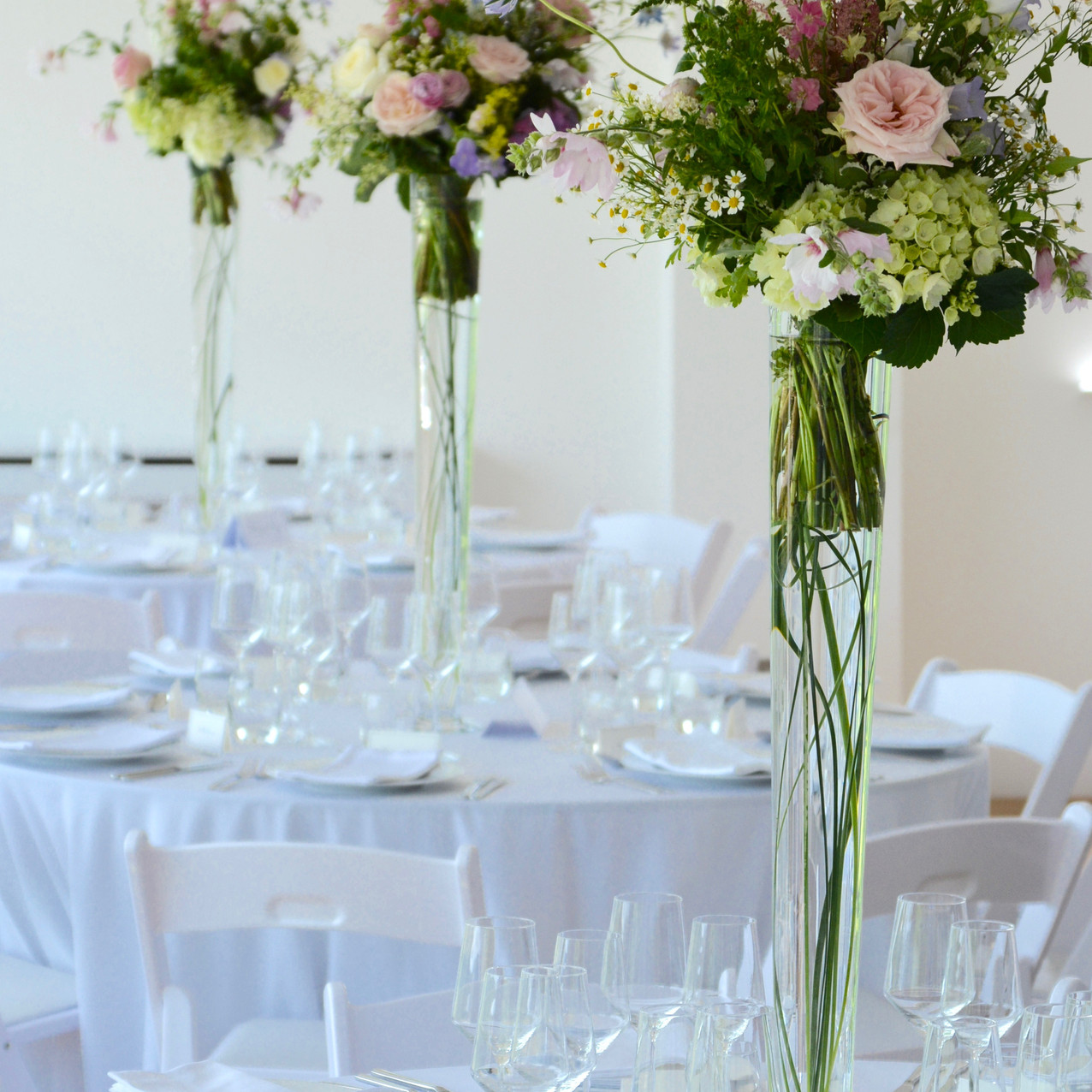Tall vases with hand-tied bouquets of summer flowers for the guest tables