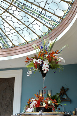 Tropical flowers in tall vase on bar