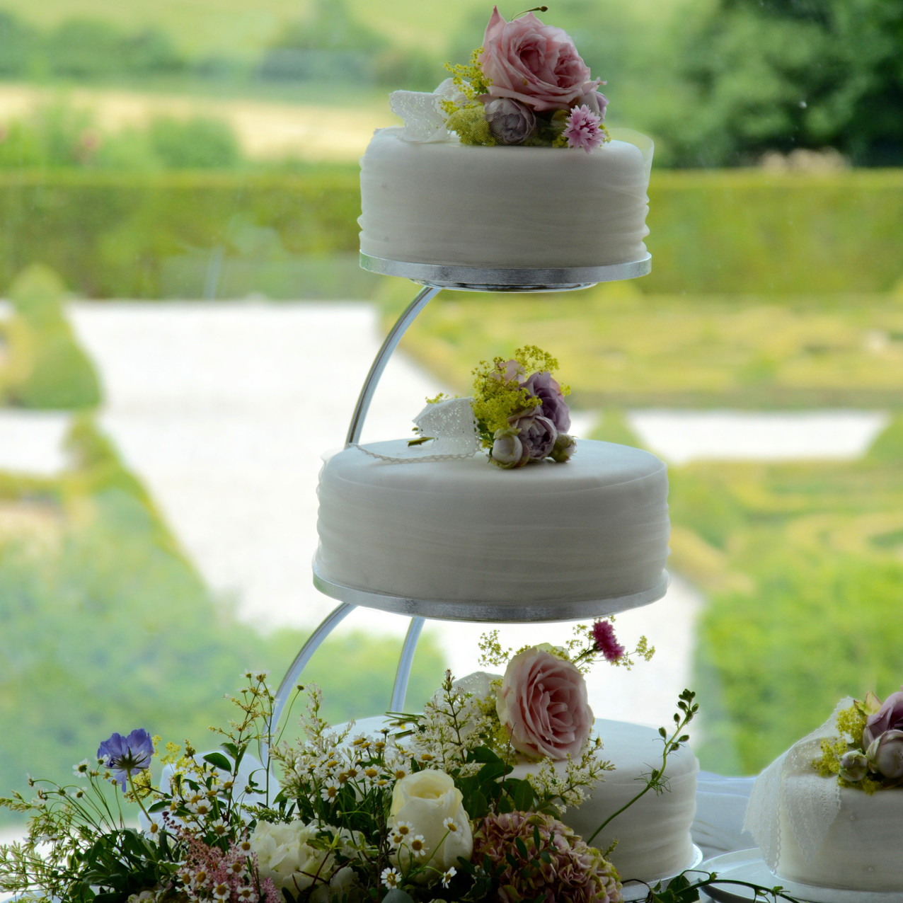 Wedding cake with corsages of flowers and view of parterre garden