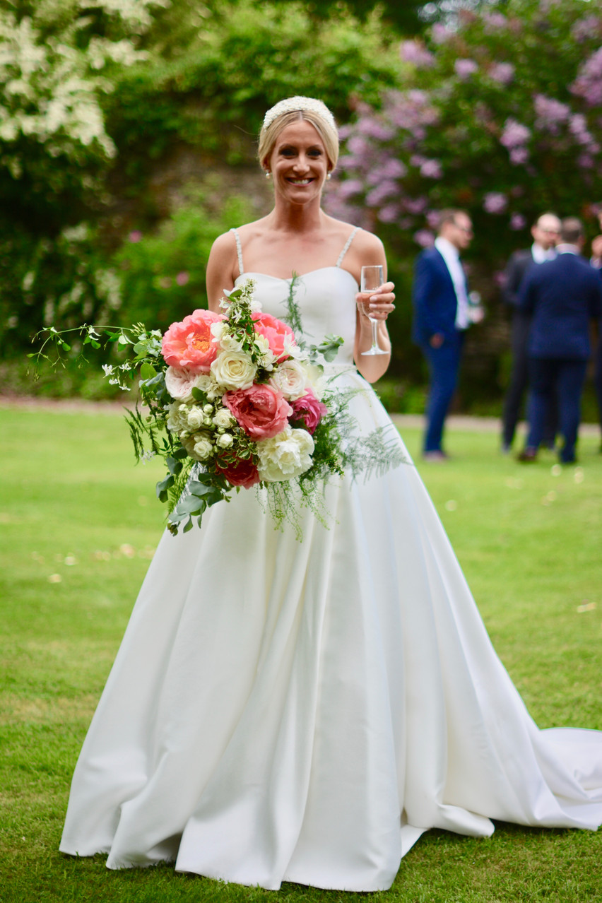 Image captured of Kate shortly after the wedding ceremony - she's holding a large bridal bouquet of ivory roses, Duchess Nemo peonies, blush O-Hara roses, ivory spray roses, spirea, thylespi, cinerea eucalyptus, asparagus fern, jasmine, pittosporum with contrasting Coral Sunset peonies