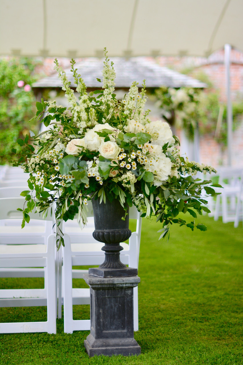 Placed at the entrance of the ceremony aisle - Classical Pedestal & Urn complete with ivory, white, blush flowers and lots of greenery.