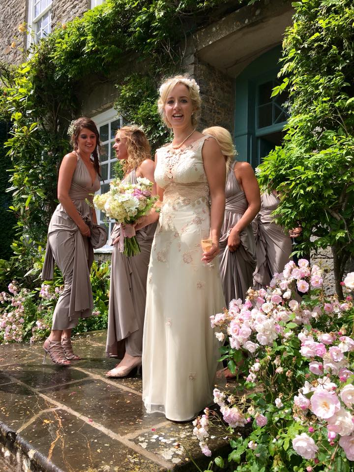 Alice the bride with her bridesmaids, holding their bouquets after the torrential rain, which didn't dampen their spirits - Dress by Claire Pettibone - http://www.clairepettibone.com/