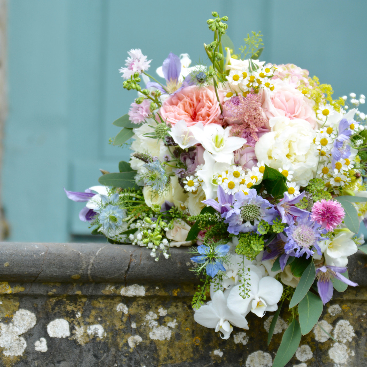 Gathered bridal bouquet of summer flowers, including roses, nigella, peony, clematis, feverfew, alchemila, larkspur, phalaenopsis orchids, oregano, cornflowers, thylaspi, scabious, astilbe, flowering mint with a touch of eucalyptus and stems semi-bound with icory cotton-lace and pearl headed pins. Blue Geranium Florist Totnes Devon