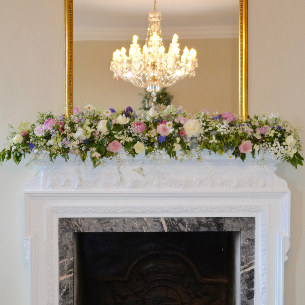 A long, slim runner arrangement of pink and cream flowers for the mantlepiece above the fireplace in the entrance hall at Kingston House