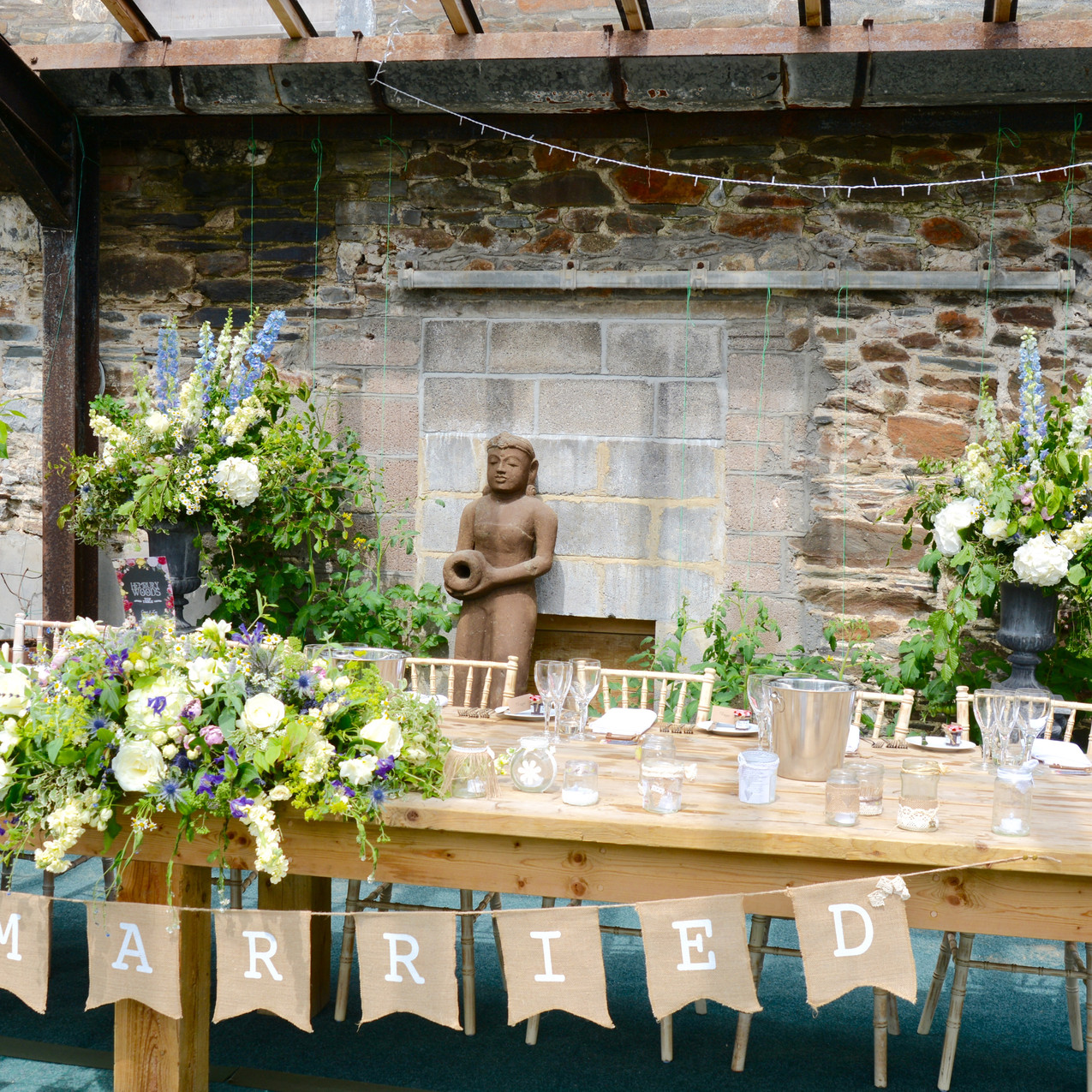 Top table flowers in the Glasshouse at Anran Barn - Complete with  two classical pedestal & urns to frame the space