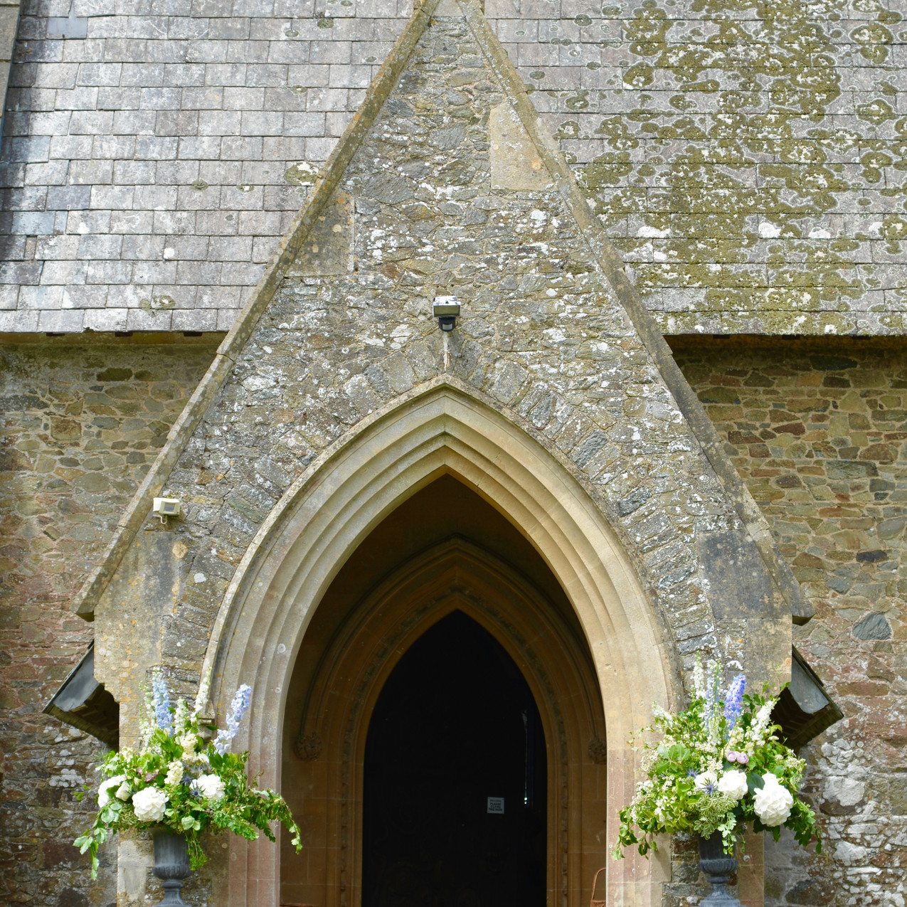 Entrance of St Matthew's church, landscove - decorated with two classical pedestal & urns, complete with natural, woodland style floral arrangements.
