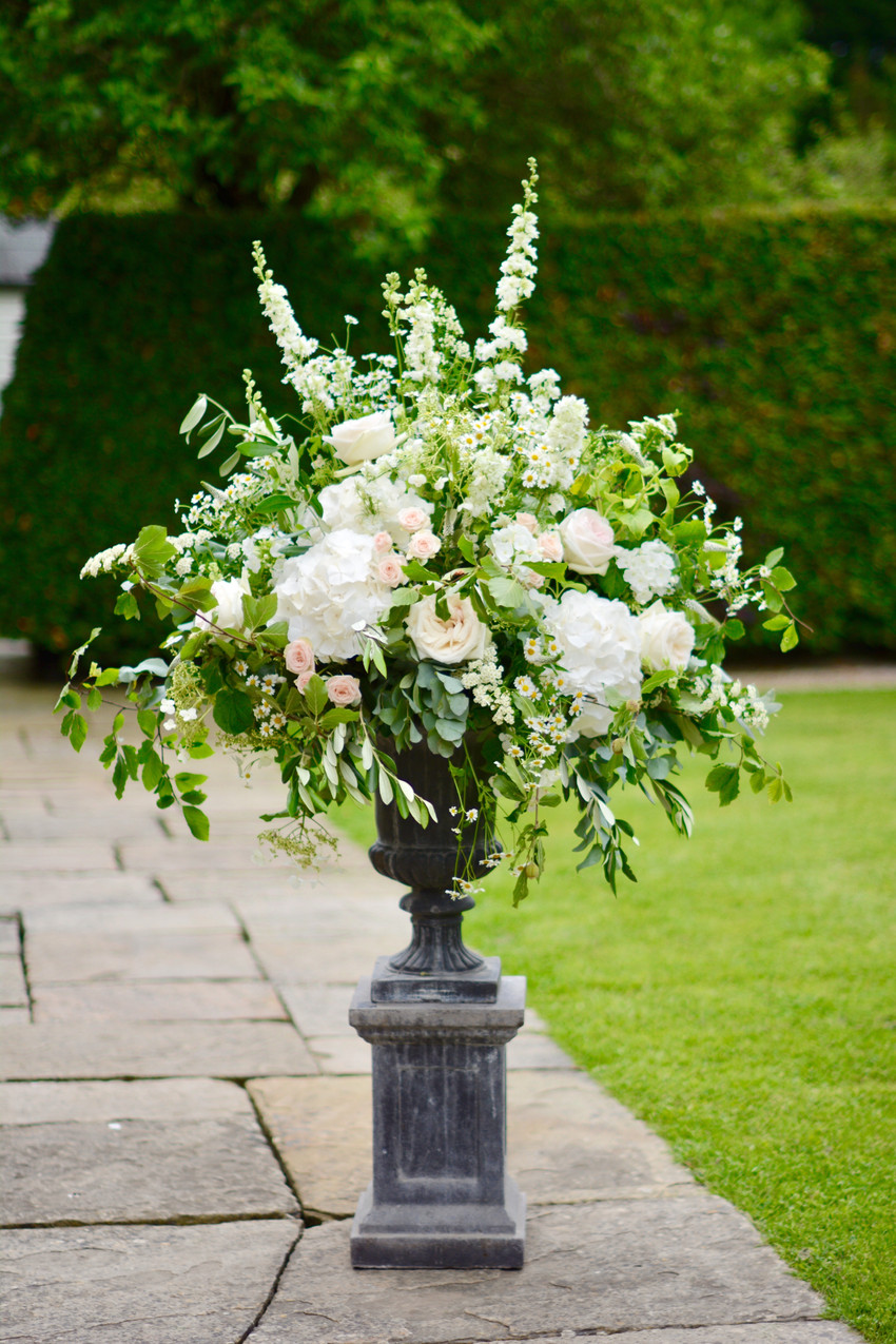 Classical Pedestal & Urn complete with ivory, white, blush flowers and lots of greenery.
