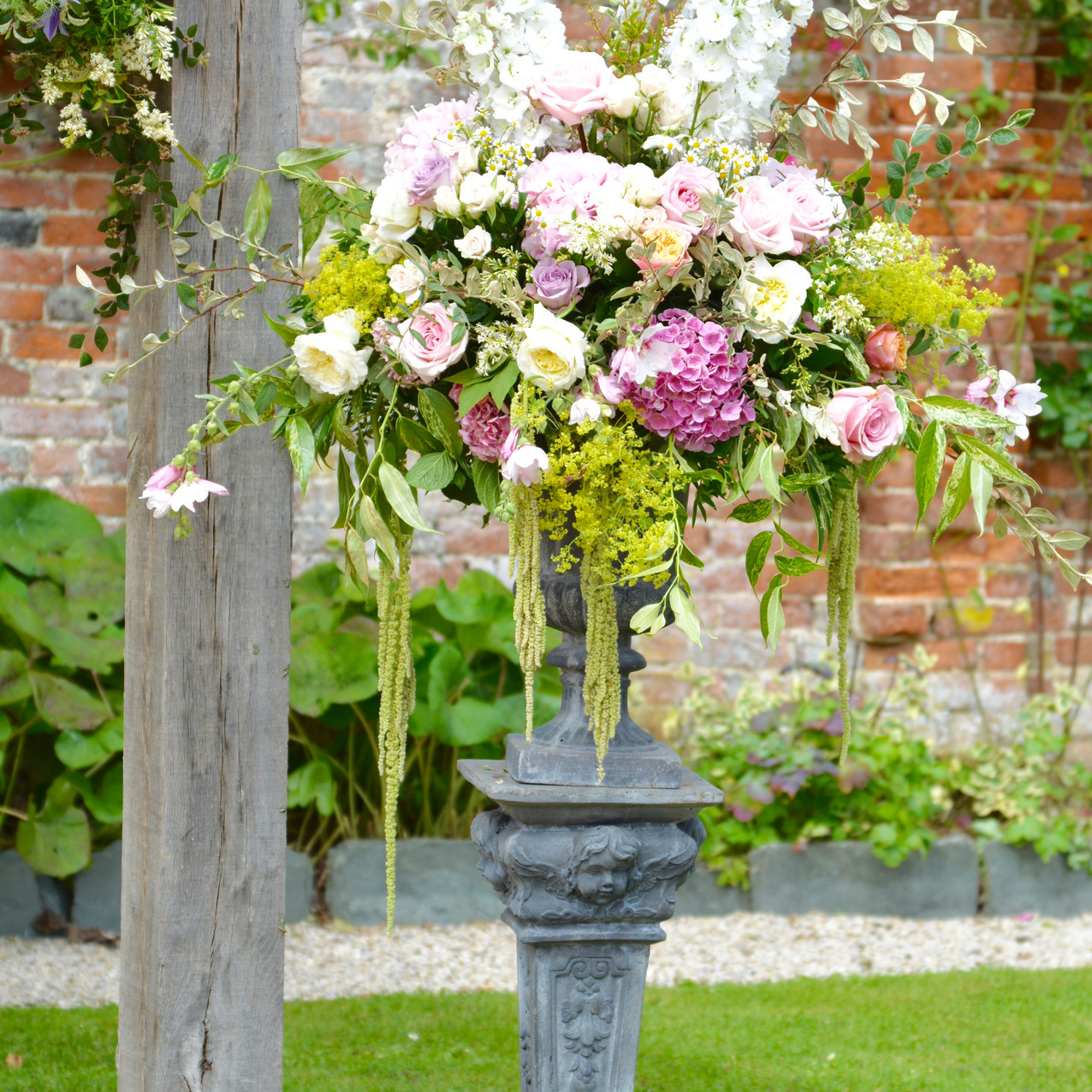 Classical Pedestal & Urn, complete with an arrangement of seasonal summer flowers and foliage. Delphinium, roses, amaranthus, hydrangeas
