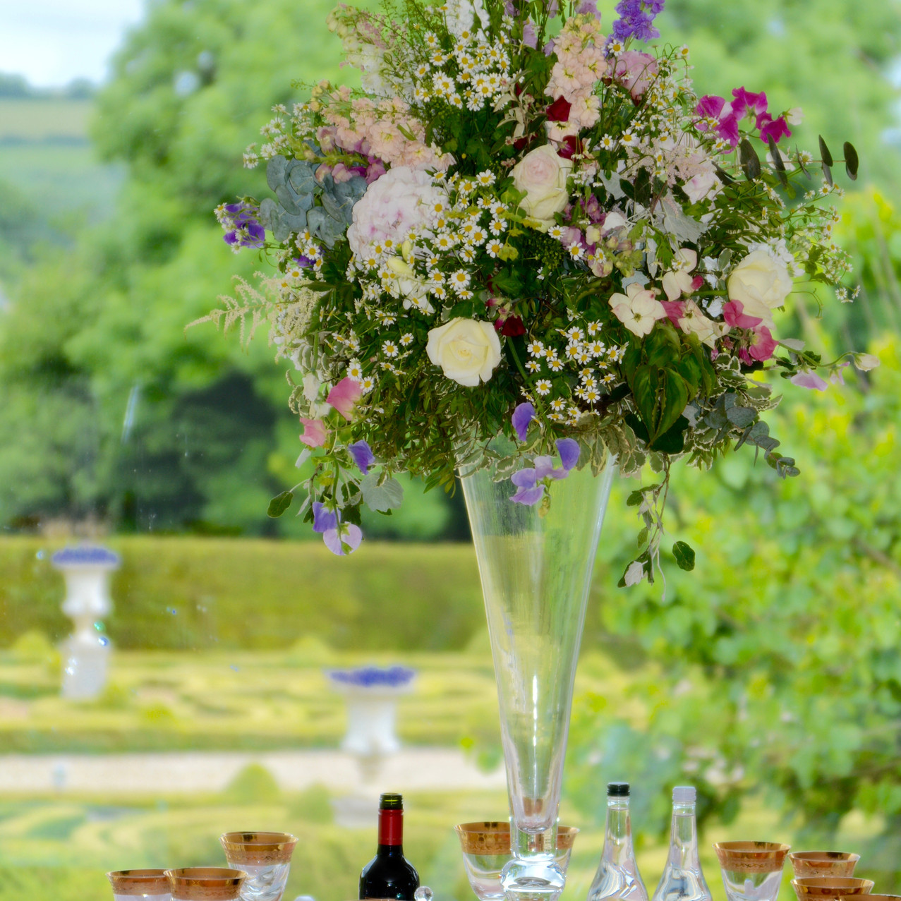 Tall (80cm) bow-tie style vase, centred on 7 of the 15 guest tables. Complete with a large garden arrangement of seasonal flowers. The designs imitated the content as seen thoughout the gardens of Kingston House.
