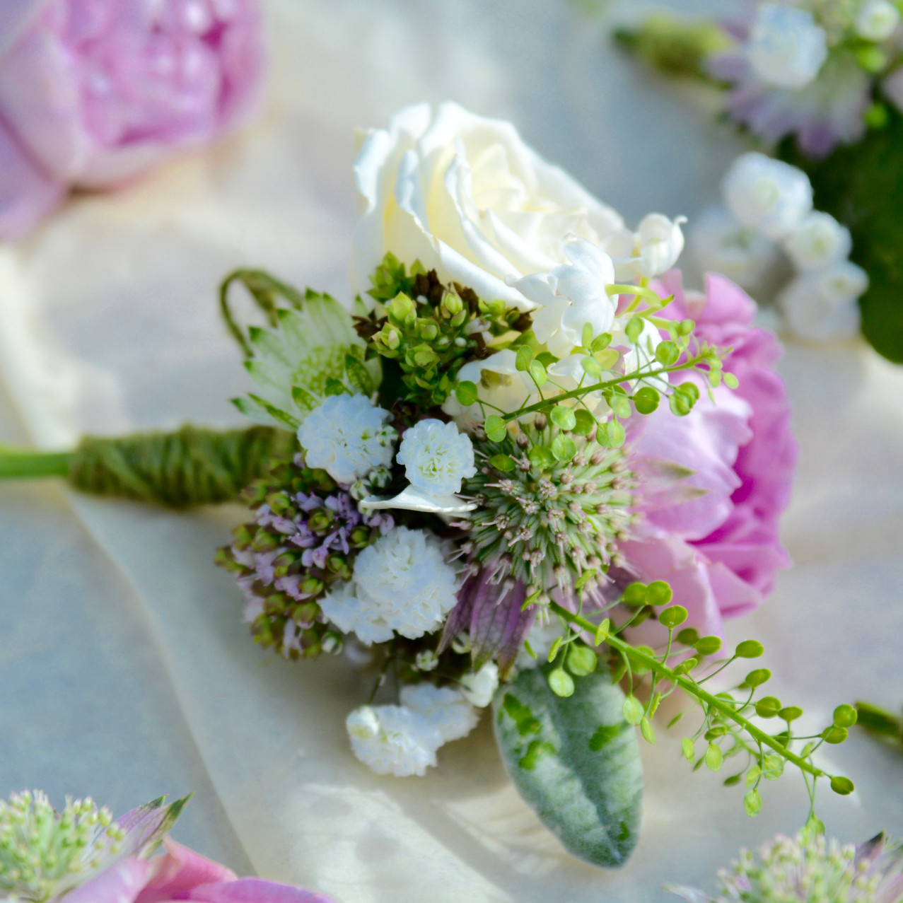 Blush pink spray rose buttonhole dressed with Lily of the Valley, ivory spray rose, oregano, thylaspi, astrantia