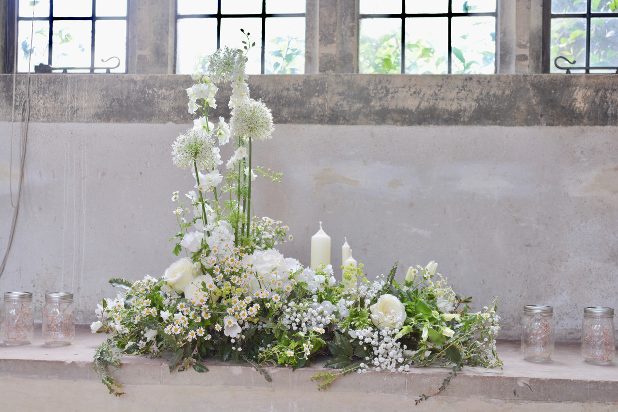 Window arrangement of seasonal ivory flowers and foliage in the Great Hall, Dartington