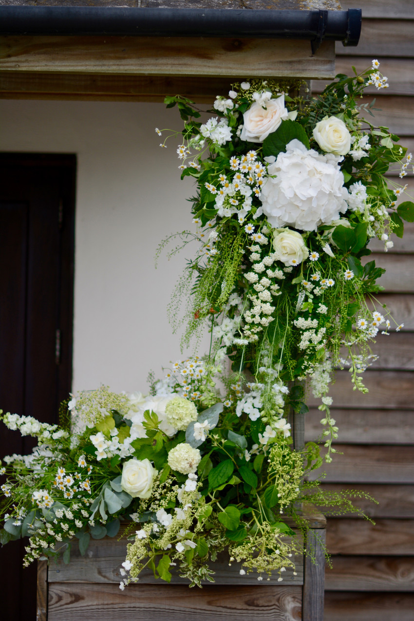 Entrance to the Barn decorated with reused floral arrangements from the ceremony gazebo.