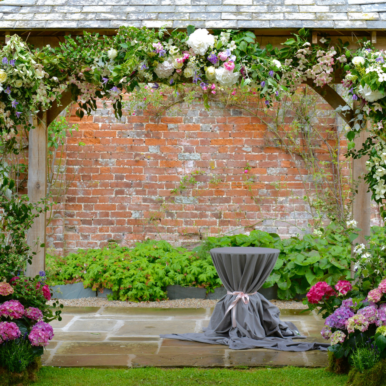Ceremony Pergola at Kingston House Estate, fully fressed with lush seasonal foliage an climbing flowers with a base of pink and white hydrangeas.