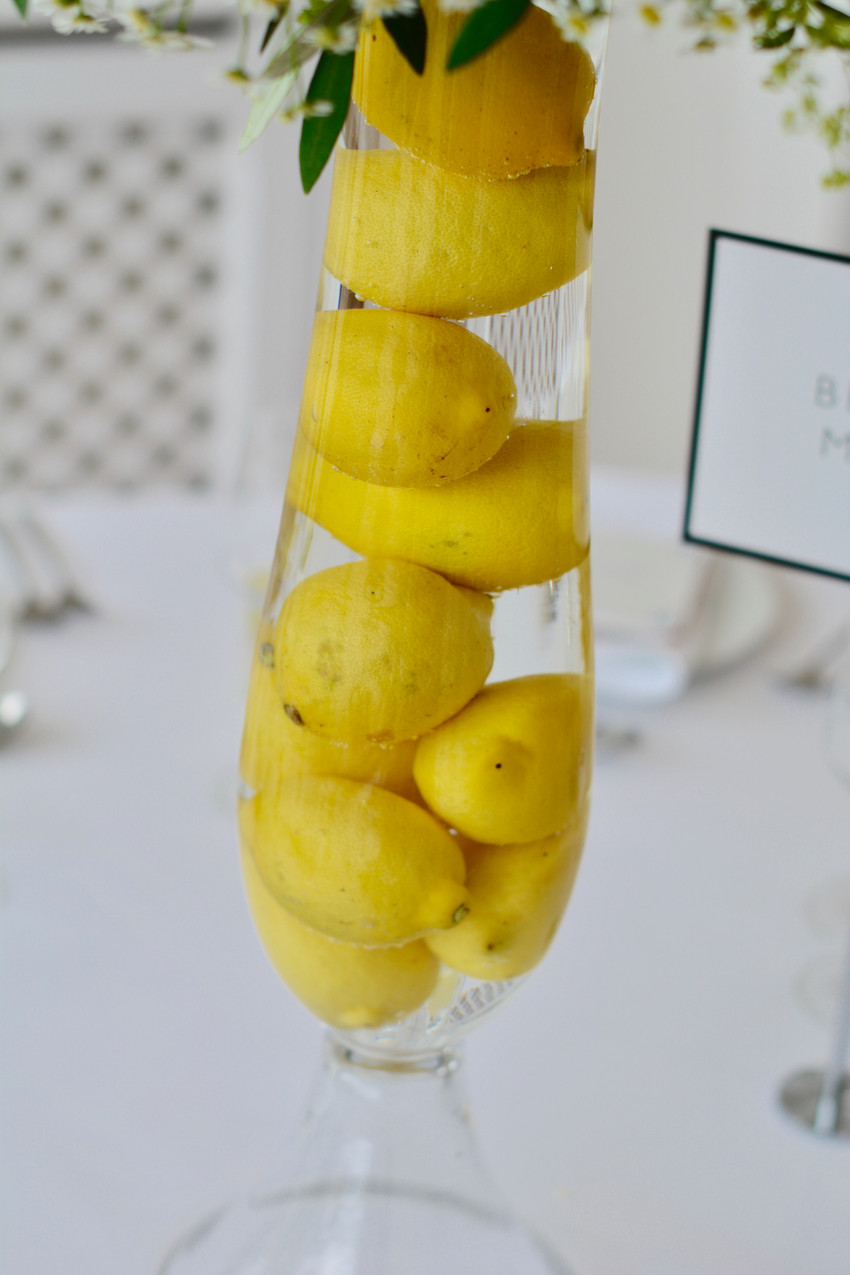 Hour glass vase filled with lemons and topped up with water.