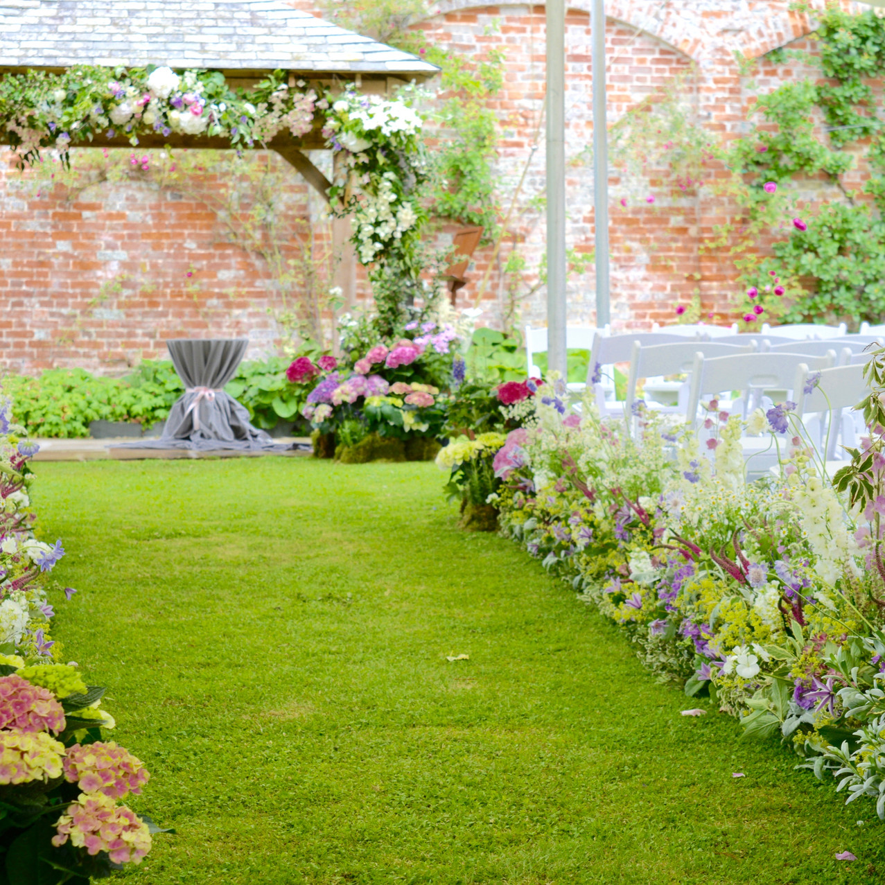 Entrance to the ceremony aisle at Kingston House Estate. A living aisle, or herbacious border was created for the happy couple to walk down towards the ceremony pegola.