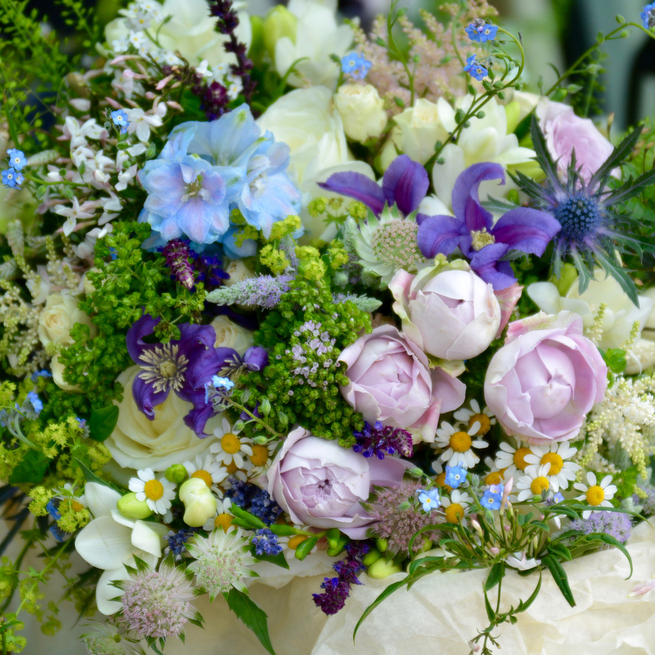 Woodland style bridal bouquet of lush green foliage and tonal blue, lilac and purple seasonal flowers, including herbs, roses, delphinium, freesias, clematis, forget-me-not, astilbe, astrantia, oregano, flowering mint, jasmine, thylaspi, feverfew, eryngium, salvia