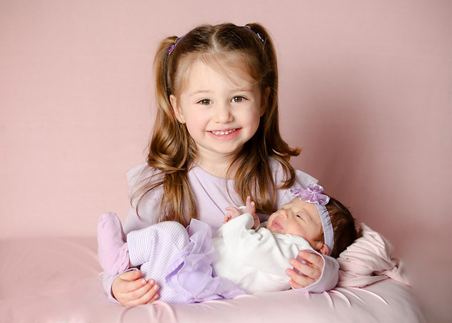 Newborn baby girl with sister