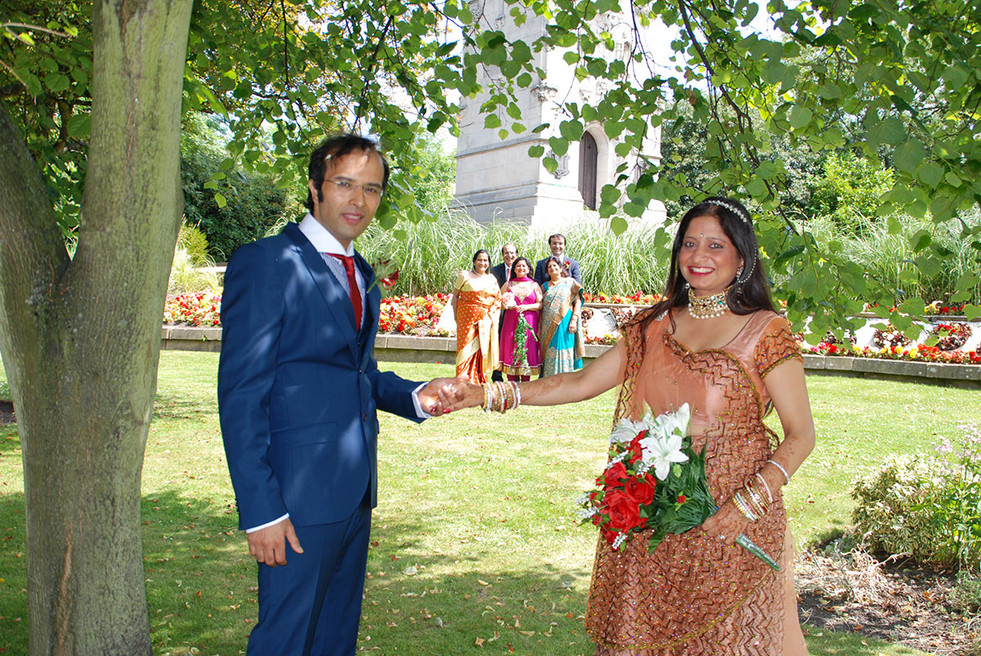 Bride & Groom holding hands with family behind. Asian wedding photography Greater Manchester