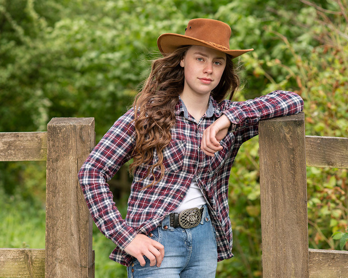 teenage girl with cowboy hat leaning on fence Greater Manchester photography Ambience Images