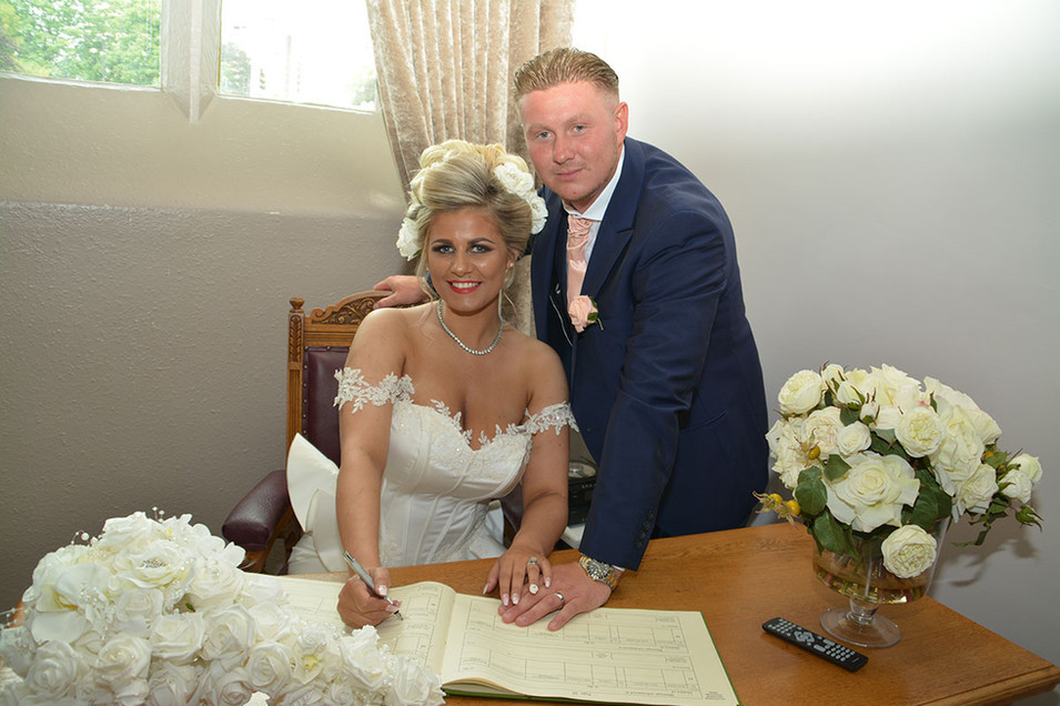 Bride & Grrom sign register with white flowers Photographer from Bury, North West Wedding photographer