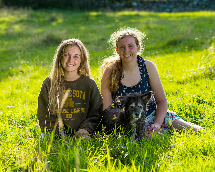 Sisters outside in grass Ambience Images potrait photographer