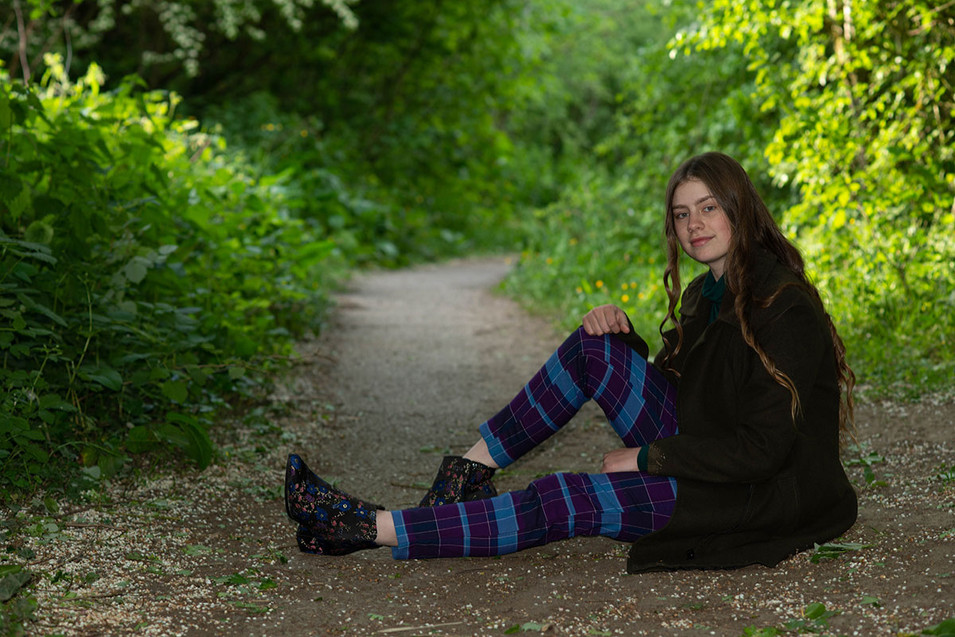 Girl sat in wooded area on path portrait photo