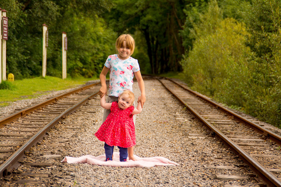 Sisters by old railway lines outdoors Greater Manchester family photographer Ambience Images