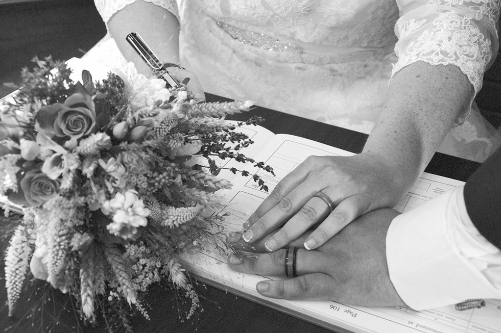 black & white close up of couples hands on wedding register photography Lancashire