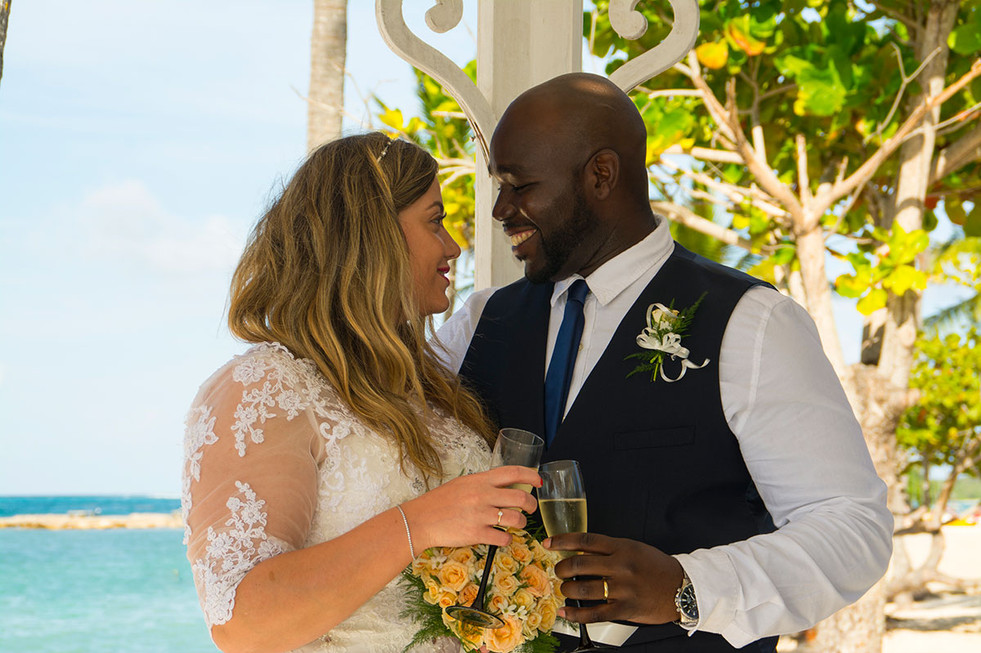 Wedding abroad, bride & groom look at each other with champagne glasses in hand Ambience Images destination wedding photography