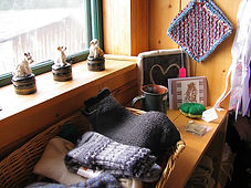 A stack of knitted socks on a shelf, and handmade pot holders hanging from a wall.