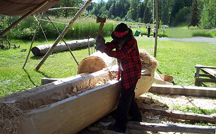 Robert Frederick works on the dugout canoe at Huble Homestead.