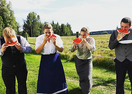 Four Huble Homestead staff members in costume eating watermelon.