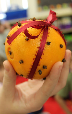 An orange stuffed with cloves to make an old-fashioned pomander ball.