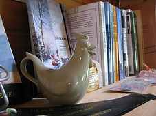 A selection of books on a shelf, with a green creamer jug shaped like a chicken in the forefront.