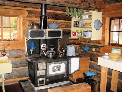 A stove inside the summer kitchen, a log cabin beside the house.