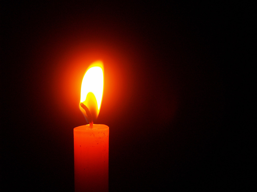 Red candle and flame burning in darkness