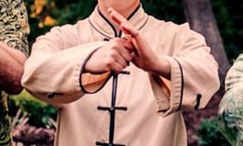 person standing Shaolin Salute white shirt
